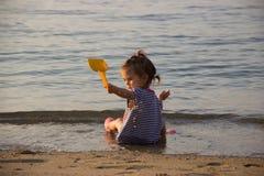 Игры маленькой девочки на пляже с лопаткоулавливателем и водой ` детей брызгают стоковое фото
