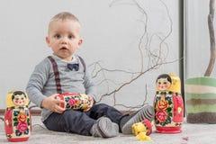 Игры мальчика с русской, который гнездят куклой Стоковое Изображение