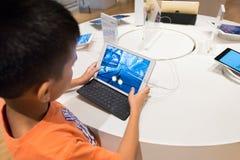 Игры мальчика на iPad, Куалае-Лумпур Стоковое фото RF