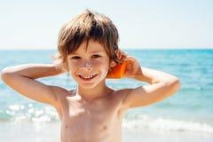 Игры мальчика с солнечной защитой Стоковые Изображения