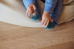 Игры младенца с его ногами Стоковые Изображения