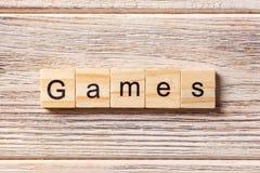 Игры формулируют написанный на деревянном блоке текст на таблице, концепция игр стоковые фото