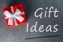 Идеи для подарка Думающ о подарки Новом Годе, дне рождества и валентинки и онлайн покупки Красная коробка присутствующая с смычко Стоковое фото RF