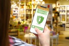 Идея безопасностью интернета, девушка с frameless телефоном на запачканной предпосылке магазина стоковые фотографии rf