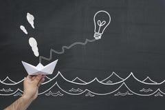 идея принципиальной схемы новая Большая идея дела делая движением бумажный корабль Стоковая Фотография