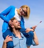 Идилличная концепция даты Человек носит подругу на плечах, предпосылку неба Женщина наслаждается совершенной романтичной датой Па стоковая фотография rf