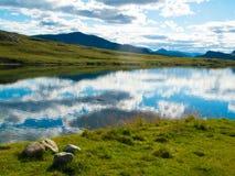 Идилличное мирное озеро с горами в горизонте Стоковая Фотография RF