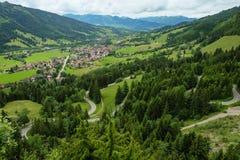 Идилличный ландшафт горы с небольшой деревней и горами на заднем плане стоковые фотографии rf