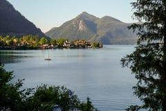 Идилличный ландшафт горы с озером, деревней и горами на заднем плане стоковые фотографии rf