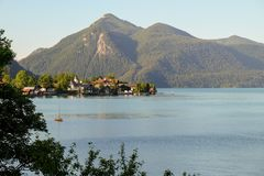 Идилличный ландшафт горы с озером, деревней и горами на заднем плане стоковое изображение rf