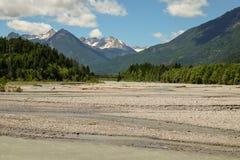 Идилличный ландшафт горы с рекой и горами на заднем плане стоковое изображение rf