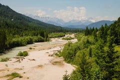Идилличный ландшафт горы с рекой и горами на заднем плане стоковые изображения