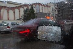 Идите дождь на улице города через лобовое стекло автомобиля Падения дождя на окне, ненастной погоде Стоковое Изображение RF