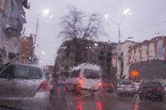 Идите дождь на улице города через лобовое стекло автомобиля Падения дождя на окне, ненастной погоде Стоковые Фото