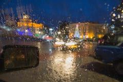 Идите дождь на улице города через лобовое стекло автомобиля Падения дождя на окне, ненастной погоде Стоковое Изображение