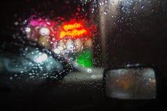 Идите дождь на улице города через лобовое стекло автомобиля Идите дождь падения на окне, ненастной погоде, ноче Стоковые Изображения RF