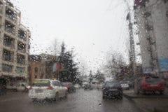 Идите дождь на улице города через лобовое стекло автомобиля Падения дождя на окне, ненастной погоде Стоковые Изображения RF