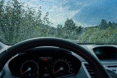 Идите дождь падения на лобовом стекле с рулевым колесом автомобиля Стоковые Фотографии RF