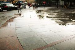 Идите дождь падения на лужице воды на городе в вечере Стоковые Изображения RF