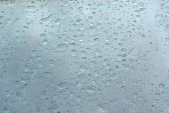 Идите дождь падения на синем стекле формируя предпосылку текстурированную водой Стоковые Фотографии RF