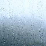 Идите дождь падения на стеклах окна отделайте поверхность с пасмурным и зеленым backg Стоковые Изображения RF