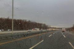 Идите дождь падения на стекле во время расплывчатых падений воды изображений на стекле автомобиля Стоковая Фотография