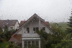 Идите дождь падения на стекле окна с взглядом к ближнему дому Стоковые Изображения