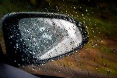 Идите дождь падения свертывая на окне красного зеркала взгляда со стороны автомобиля Стоковое фото RF