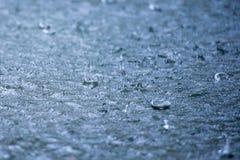 Идите дождь падения струясь в лужице с отражением голубого неба Стоковая Фотография RF