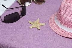 Идти на каникулы на пляже Шляпа для защиты от солнца и пары солнечных очков На фоне пляжного полотенца Стоковые Изображения RF