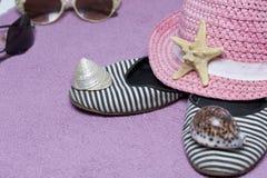 Идти на каникулы на пляже Шляпа для защиты от солнца и пары солнечных очков Тапки и морские звёзды пляжа Против Стоковые Изображения