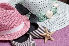 Идти на каникулы на пляже Шляпа для защиты от солнца и пары солнечных очков Тапки и морские звёзды пляжа Против Стоковое Изображение