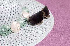 Идти на каникулы на пляже Шляпа для защиты от солнца и пары солнечных очков На фоне пляжного полотенца Стоковые Изображения