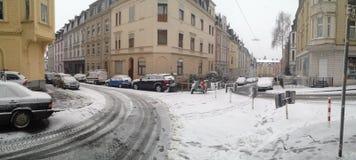 Идти снег в холмистом угле улицы в Вуппертале, Германия с припаркованными автомобилями стоковая фотография rf