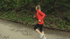 Идущая девушка Белокурая девушка делая внешние спорт в замедлении взгляда со стороны леса лета широкоформатном акции видеоматериалы