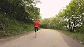 Идущая девушка Белокурая девушка делая внешние спорт в замедлении взгляда со стороны леса лета широкоформатном сток-видео