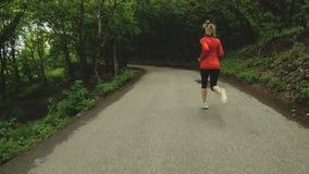 Идущая девушка Белокурая девушка делая внешние спорт в замедлении вид сзади леса лета широкоформатном акции видеоматериалы