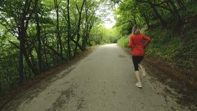 Идущая девушка Белокурая девушка делая внешние спорт в замедлении вид сзади леса лета широкоформатном сток-видео