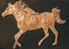 Идущая лошадь Символ покрашенный золотом лошади стоковое изображение