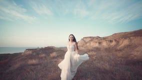 Идущая невеста в изумлять длинное платье через ландшафт видеоматериал