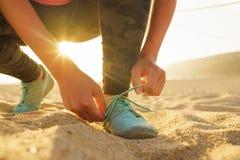 Идущие ботинки - женщина связывая шнурки ботинка на песчаном пляже на заходе солнца Стоковые Фотографии RF
