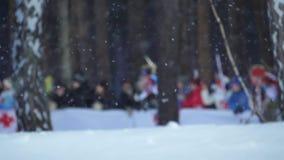Идущие спортсмены биатлона в defocus на предпосылке падая замедленного движения снега видеоматериал