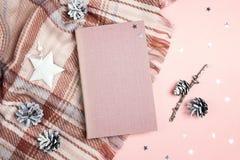 Идущий сверху вниз состав зимних отдыхов с книгой, шотландкой, конусами и звездами на розовой предпосылке стоковое фото rf