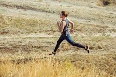 идущий спорт Sprinting бегунка человека напольный в сценарной природе Подходящий мышечный мужской след тренировки спортсмена бежа Стоковое фото RF