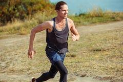 идущий спорт Sprinting бегунка человека напольный в сценарной природе Подходящий мышечный мужской след тренировки спортсмена бежа Стоковая Фотография RF