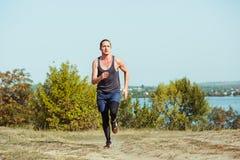идущий спорт Sprinting бегунка человека напольный в сценарной природе Подходящий мышечный мужской след тренировки спортсмена бежа Стоковые Изображения