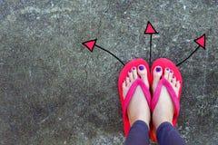 Идя нарисованные направления стрелок Положение темпового сальто сальто носки женщины красное и желтое на предпосылке цемента Стоковое фото RF