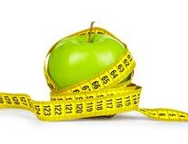 диетпитание принципиальной схемы Зеленое яблоко и желтая измеряя лента на isolat Стоковое фото RF
