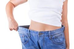 диетпитание принципиальной схемы Тонкие женщины в больших джинсах показывая успешный вес стоковое фото