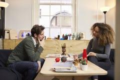 2 дизайнера имея творческую встречу в современном офисе Стоковое фото RF